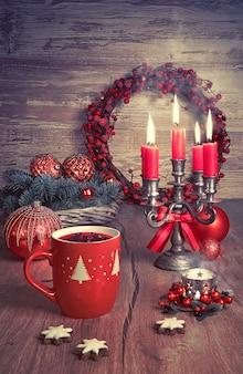 Vino caliente, galletas de navidad y velas en la mesa decorada