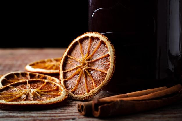 Vino caliente hecho en casa, naranjas secas y canela en una mesa de madera sobre un fondo oscuro