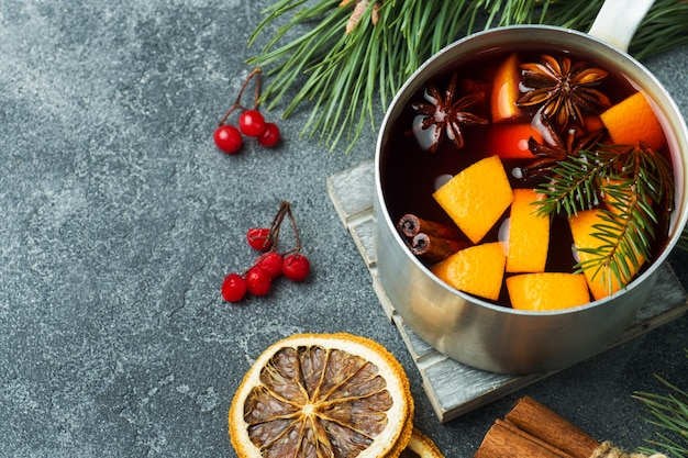 Vino caliente de navidad con especias y frutas sobre la mesa.