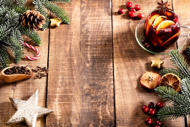 Vino caliente de navidad con especias sobre una mesa rústica de madera.