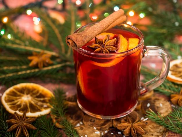 Vino caliente de navidad con naranjas y especias decoraciones navideñas con bokeh