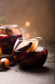 Vino caliente de navidad en vasos circulares deliciosas vacaciones como fiestas con especias de anís estrellado de canela. bebida caliente tradicional en vasos circulares o bebidas, cóctel festivo en navidad o año nuevo