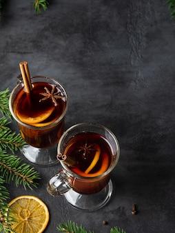 Vino caliente con rodajas de naranja, estrellas de anís, especias y palitos de canela sobre fondo oscuro con ramas de spruse. navidad y año nuevo diseño plano. vista superior de bebidas.