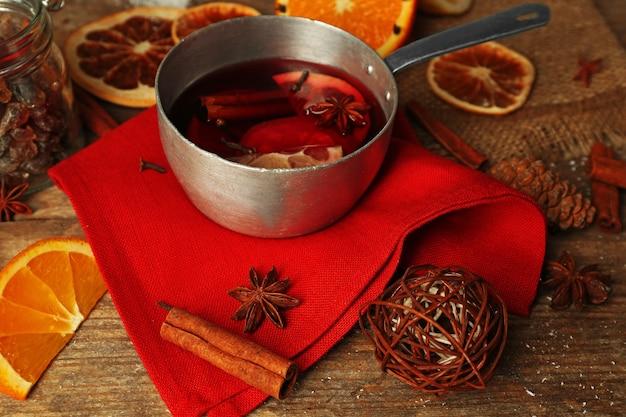 Vino caliente en sartén sobre decorado con servilleta roja, canela y fondo de madera naranja