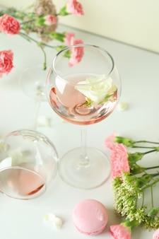 Vino, dulces y flores en la mesa blanca