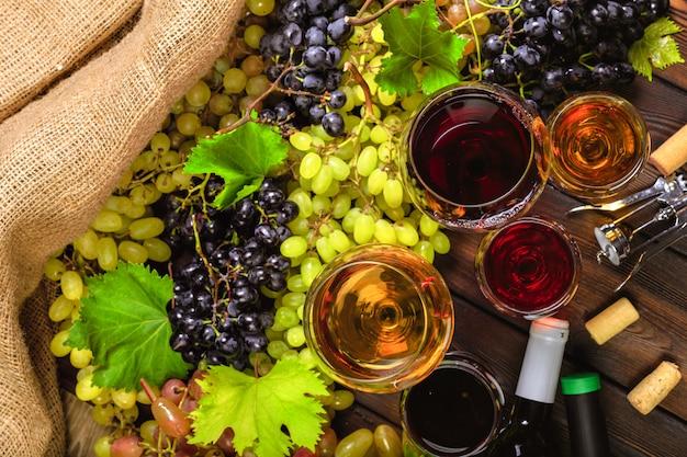 Vino con ramas de uvas blancas. en una mesa de madera.
