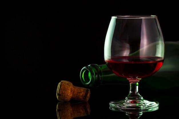 Vino rojo en vidrio y botellas en la tabla en fondo de la oscuridad.