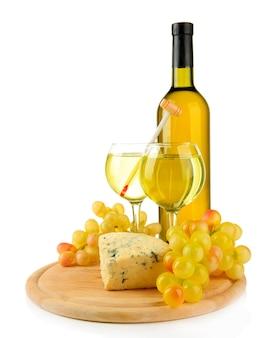 Vino, sabroso queso azul y uva en tabla de cortar, aislado en blanco
