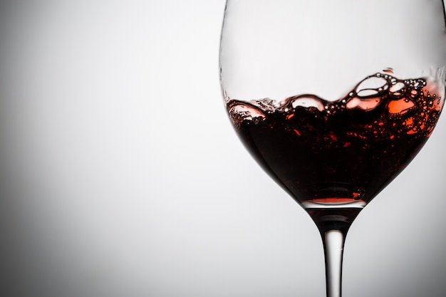 Vino tinto con burbujas en copa de vino.