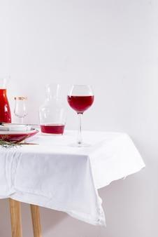 Vino tinto en copa de vino, jarra y mesa con sombras