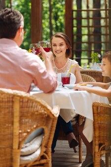 Vino tinto. dos padres radiantes bebiendo vino tinto mientras celebran el cumpleaños de su pequeño y lindo hijo