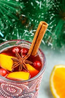 Vino tinto especiado tradicional de navidad con especias (canela, anís estrellado, cardamomo) y frutas (cítricos, arándanos, manzanas)