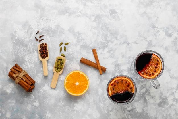 Vino tinto glintwine servido en vasos para la mesa de navidad con naranja y especias