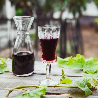 Vino tinto en jarra y vaso con vista lateral de rama de árbol de uva en mesa de madera y jardín