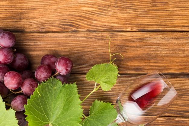 Vino tinto y uvas en mesa de madera.