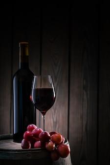 Vino tinto en vidrio y botella de pie en barril con racimo de uvas
