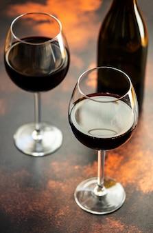 Vino tinto en un vidrio, primer plano, enfoque selectivo. una botella de vino tinto y dos vasos sobre la mesa. vertical