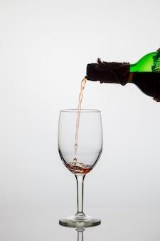 El vino tinto se vierte en un vaso sobre fondo blanco.