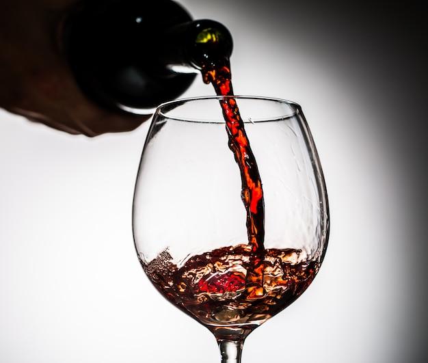 Vino de uva vertido de botella en copa de vino de vidrio