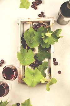 Vino y uvas sobre fondo de mármol gris