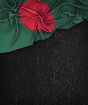 Vintage de la bandera de bangladesh en una pizarra negra del grunge con el espacio para el texto