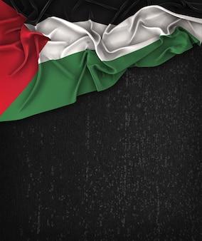 Vintage de la bandera de palestina en una pizarra negra del grunge con el espacio para el texto