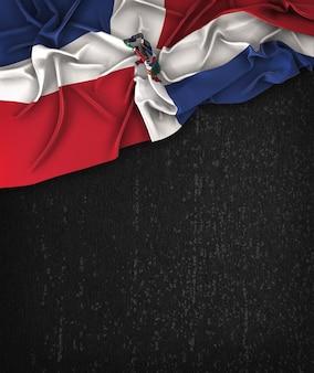 Vintage de la bandera de la república dominicana en una pizarra negra del grunge con el espacio para el texto