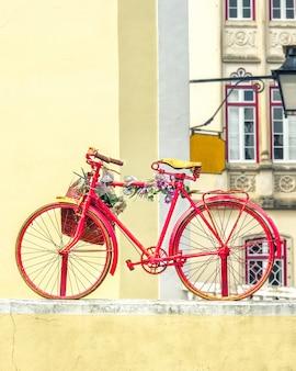 Vintage bicicleta roja antigua decorada con flores y una cesta.