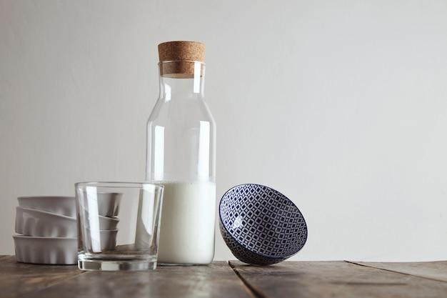 Vintage botella de corcho cerrado con leche en la mesa de madera envejecida cerca de whisky rox vidrio transparente, platos de cerámica blanca y cuenco con patrón esmaltado, aislado en blanco