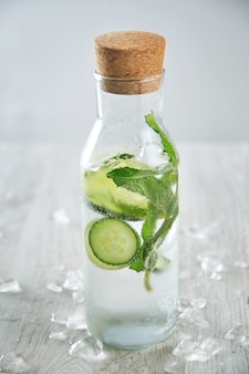 Vintage botella de vidrio llena de limonada de limón y menta fresca fría como mojito sin alcohol