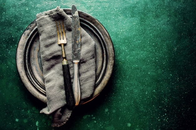 Vintage cubiertos en plato en mesa verde