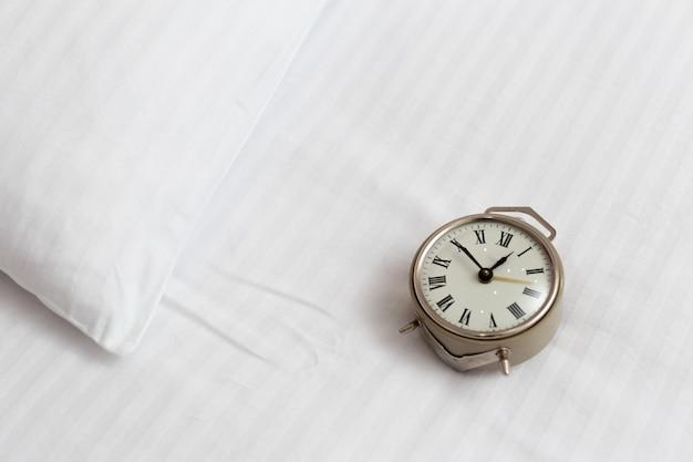 Vintage despertador en una cama en una habitación de hotel. concepto de llamada de despertador