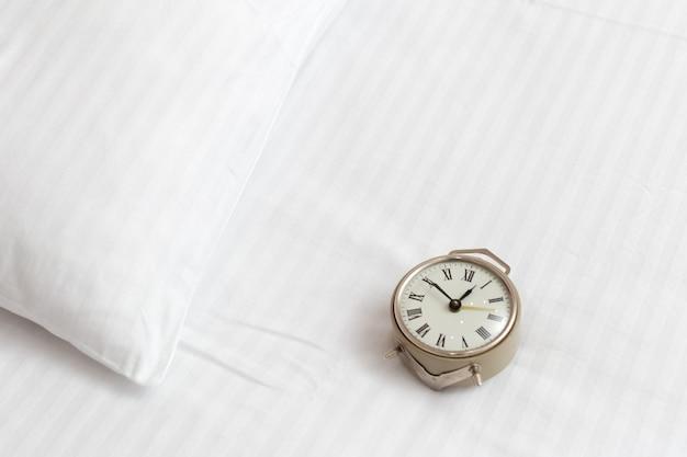 Vintage despertador en una cama en una habitación de hotel. llamada de atención