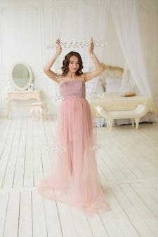 Vintage hermosa mujer embarazada en vestido rosa posando benind chandellier