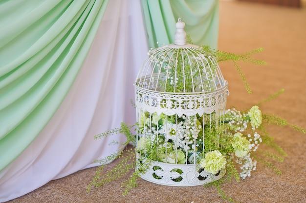 Vintage jaula de pájaros decorada con corona de flores, rosas pequeñas, crisantemos