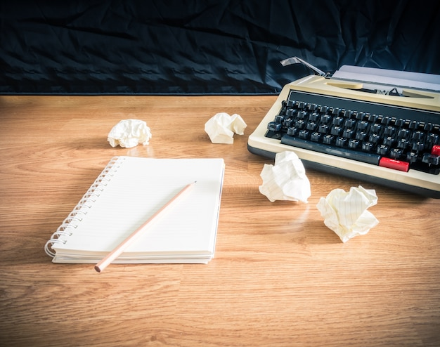 Vintage máquina de escribir y un cuaderno de papel en blanco