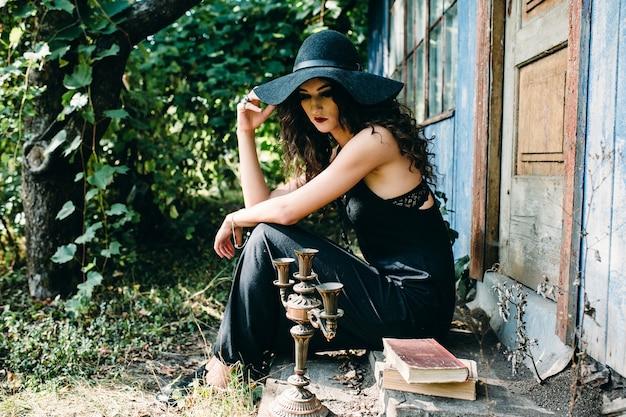 Vintage mujer como bruja, posando junto a un edificio abandonado en vísperas de halloween