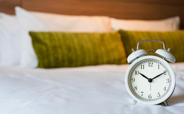 Vintage reloj despertador blanco en el dormitorio.