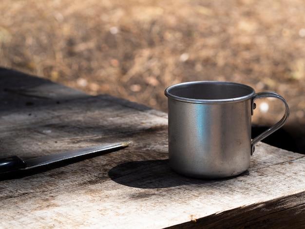 Vintage taza de metal y un cuchillo en la mesa de madera en mal estado