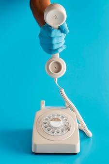 Vintage teléfono con la mano en el guante sosteniendo el receptor