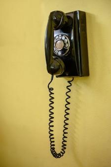 Vintage teléfono negro en una pared.