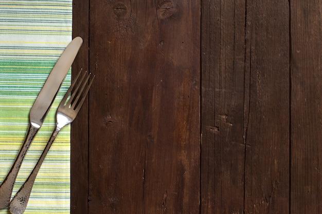 Vintage tenedor y cuchillo en una colorida servilleta sobre mesa de madera