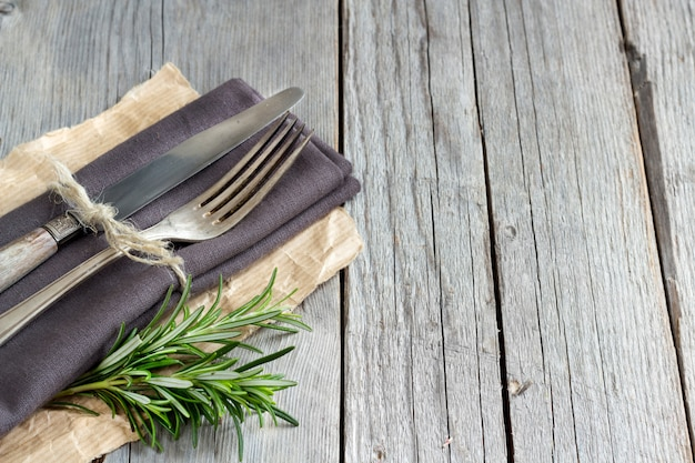 Vintage tenedor y cuchillo en servilleta gris con romero fresco en la mesa de madera de cerca con espacio de copia