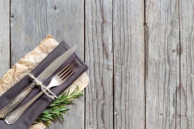 Vintage tenedor y cuchillo en servilleta gris con romero fresco en la vista superior de la mesa de madera con espacio de copia