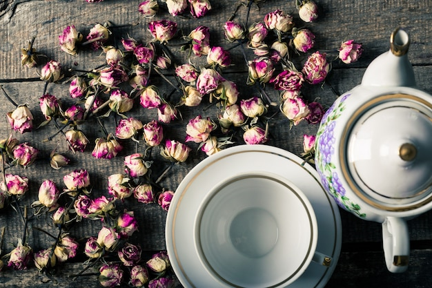 Vintage tetera y taza con flores de té floreciente en superficie de madera