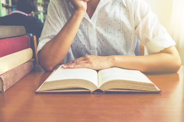 Vintage tono de asia mujer libro de lectura en la biblioteca .retro efecto de filtro, enfoque suave, luz baja (atención selectiva)