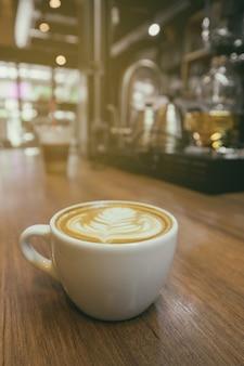 Vintage tono taza de café con leche arte. café del capuchino en la tabla de madera con el fondo del café de la falta de definición.