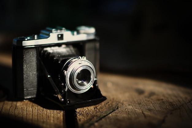 Vintage vieja cámara sobre una mesa de madera. estilo retro, nostalgia - foto de efecto vintage