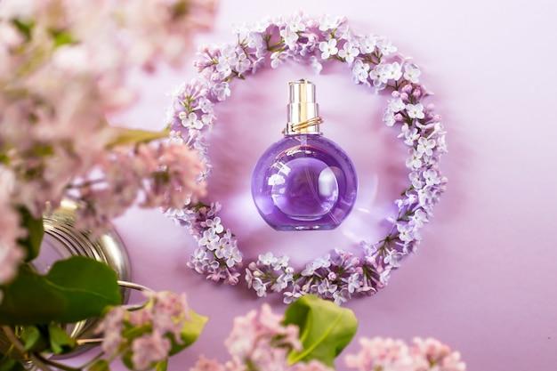 Violeta botella de perfume de mujer junto a las flores de color lila.