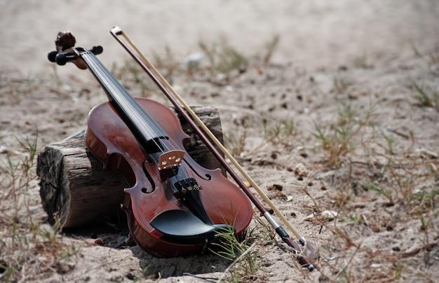 El violín y el arco de madera colocados al lado del tablero de madera, en la playa, con luz borrosa alrededor